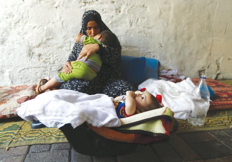 אישה פלסטינית עם ילדיה בעזה
