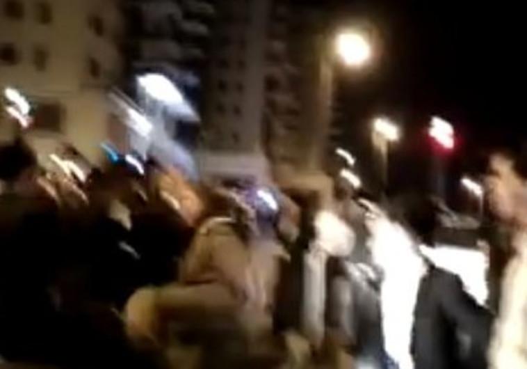 חיילת עומדת מול קבוצת מפגינים חרדיים
