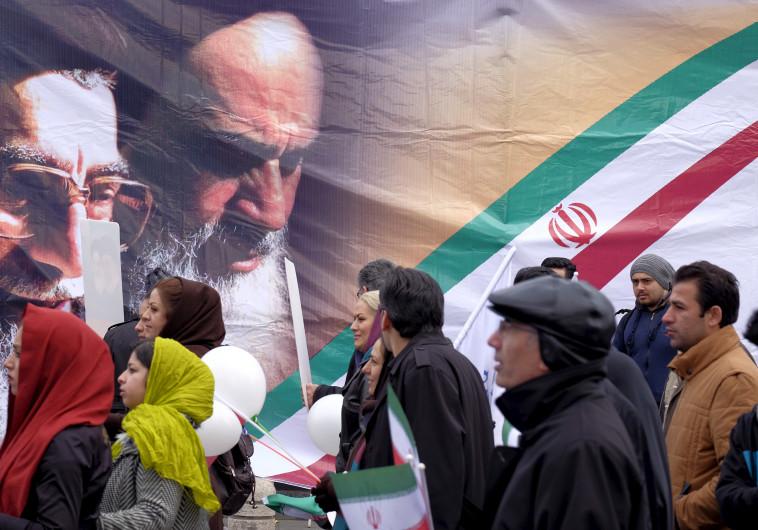 איראנים מול כרזות של חומייני וחמנאי בטהרן