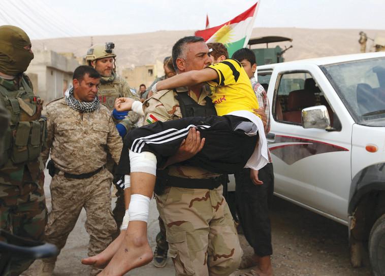 חיילים כורדים ונער פצוע, הלחימה בדאעש. צילום: רויטרס