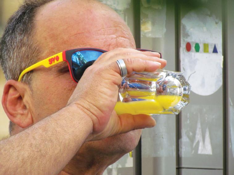 את העדשה שלי תופס גבר במשקפיים צהובים, שותה מיץ תפוזים צהוב. צילום: נתן זהבי