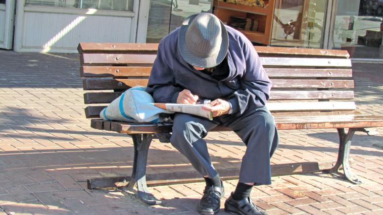 על ספסל ברחוב ויצמן יושב קשיש ופותר תשבץ. צילום: נתן זהבי
