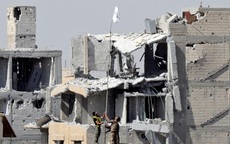 הכוחות הדמוקרטיים הסוריים מניפים דגל בא-רקה. צילום: רויטרס