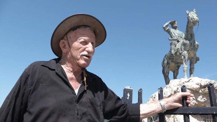 """אריק נחמקין על רקע פסלו של אלכסנדר זייד, מתוך הסרט """"לצדי רכבת העמק"""""""