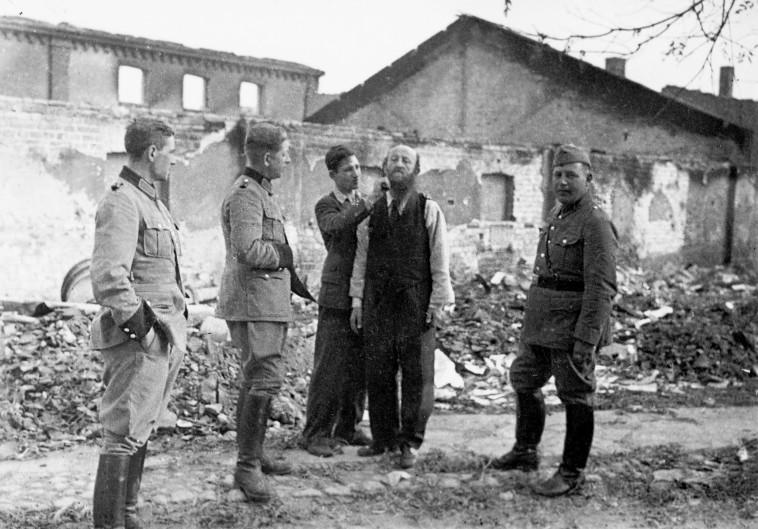 פולני מגלח ליהודי את שערו בפני חיילים גרמנים, 1939. צילום: גטי אימג'ז