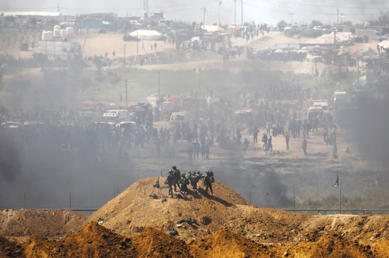 חיילים ישראלים ופלסטינים על הגדר בגבול עזה-ישראל. צילום: רויטרס