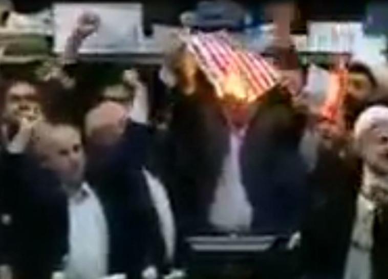 """חברי פרלמנט איראנים שורפים את דגל ארה""""ב. צילום מסך"""
