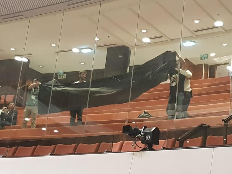 פעילי שלום עכשיו מניפים דגל שחור במהלך הדיון על חוק הלאום