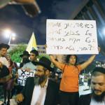 """אישה מפגינה ליד אירוע """"משיח בכיכר"""""""
