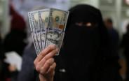 עובדת חמאס בעזה מציגה דולרים לאחר שקיבלה משכורת מקטאר