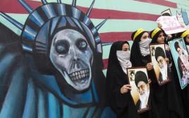 מפגינות איראניות מחזיקות בתמונתו של חמינאי לפני ציור אנטי אמריקאי