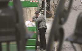 קשיש מחפש אוכל בפח אשפה בירושלים