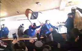 שוטר מטיח כיסא לעבר מתבצרים בעמונה