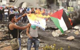 פלסטינים מציתים את דגל ישראל
