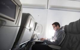 איש עם לפטופ במטוס