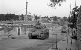 טור טנקים בתנועה לכיבוש הצד הירדני של ירושלים. מאחורי הטנקים נעים כוחות על משאיות.