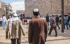 יהודי חובש כיפה וערבי עם כאפייה בירושלים