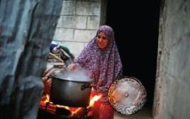 אישה מבשלת במהלך הפסקת חשמל בעזה
