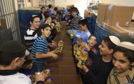 מתנדבים אורזים משלוחי מזון בעמותת חסדי נעמי