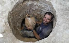ארכיאולוג רשות העתיקות עם כלי שאותר בחפירות