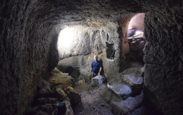 מפקח רשות העתיקות בתוך מערכת המערות החצובה בכפר עילבון
