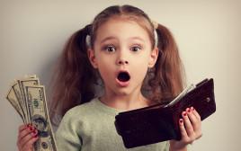 ילדה קטנה מחזיקה כסף, צילום אילוסטרציה