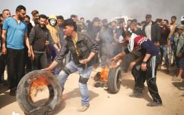 פלסטינים מבעירים צמיגים בהפגנה בגבול רצועת עזה