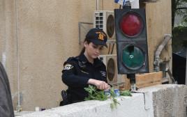 שוטרת מדליקה נרות בכניסה למכינה