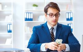 גבר בחליפה מחזיק כסף, צילום אילוסטרציה