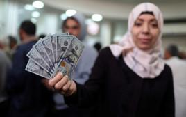 עובדת חמאס מציגה דולרים לאחר שקיבלה את משכורתה
