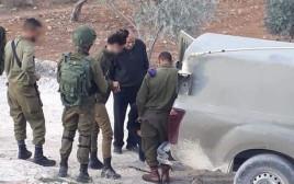 קצין פלסטיני עוזר לחיילים להחליף גלגל