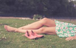 אילוסטרציה - בחורה שוכבת על הדשא