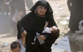 פליטה סורית חוצה את הגבול לטורקיה עם ילדיה