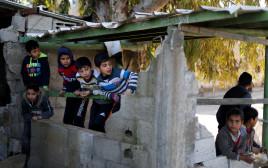 ילדים פלסטינים בבניין הרוס של חמאס בעזה