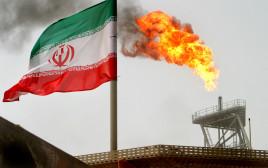 דגל איראן על רקע מתקן ייצור נפט במפרץ הפרסי
