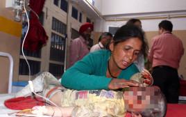 אם עם בנה שנפצע בתאונה בצפון הודו