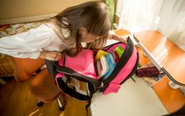 ילדה מכינה את התיק לשנת הלימודים, אילוסטרציה (המצולמת אינה קשורה לתוכן הכתבה)