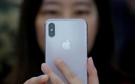 אישה מחזיקה אייפון איקס, אילוסטרציה (למצולמת אין קשר לנאמר בכתבה)