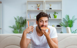 גבר אוכל פיצה בבית מול הטלוויזיה