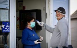 בהלת הקורונה: מאבטח מבצע בדיקת חום בכניסה לסופר באור יהודה