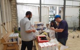 """מתנדבים אורזים חבילות לצמי""""ד"""