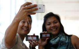אנשים מסתכלים על האייפון SE בחנות של אפל בטוקיו