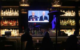 אנשים צופים בעימות בין דונלד טראמפ לג'ו ביידן