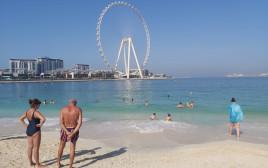 נופשים בחוף הים סמוך למרינה בדובאי