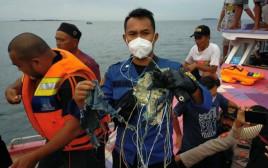 דייגים עם שרידי המטוס שהתרסק באינדונזיה