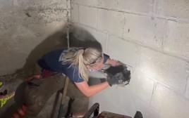 הכבאית ג'ני אדקינס מחלצת את הכלבה האבודה