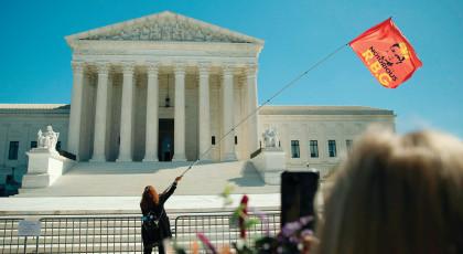 אישה מנופפת בדגל הנושא את דמותה של רות ביידר גינסבורג(צילום: אישה מנופפת בדגל הנושא את דמותה של רות ביידר גינסבורג)
