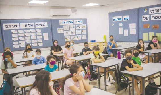 ילדים לומדים בכיתה עם מסיכות