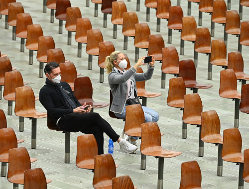 קורונה - אנשים עם מסכה צופים בדרשה השבועית של האפיפיור