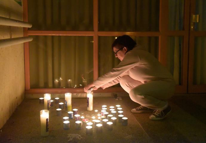 נרות נשמה מחוץ לקופת חולים לזכר האחות שנרצחה